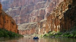 Boat in distance on Colorado River. Canyon walls.