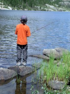Photo of a boy fishing on the shores of a lake.